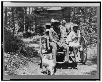 Lange, Dorothea, photographer. Colored sharecropper and his children about to leave home through the pine woods after their morning work at the tobacco farm stringing and putting up tobacco. Shoofly, Granville County, North Carolina. Granville County North Carolina Shoofly United States, 1939. July. Photograph. Retrieved from the Library of Congress, https://lccn.loc.gov/2017772361. (Accessed November 02, 2017.)