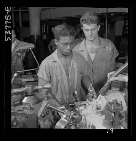 Fritz Henle, photographer. NYA National Youth Administration work center, Brooklyn, New York. A Negro bench-lathe worker, who is receiving training in machine shop practice, gauging a screw just removed from the collet. New York New York State United States, 1942. Aug.?. Photograph. Retrieved from the Library of Congress, https://lccn.loc.gov/2017866473. (Accessed November 02, 2017.)
